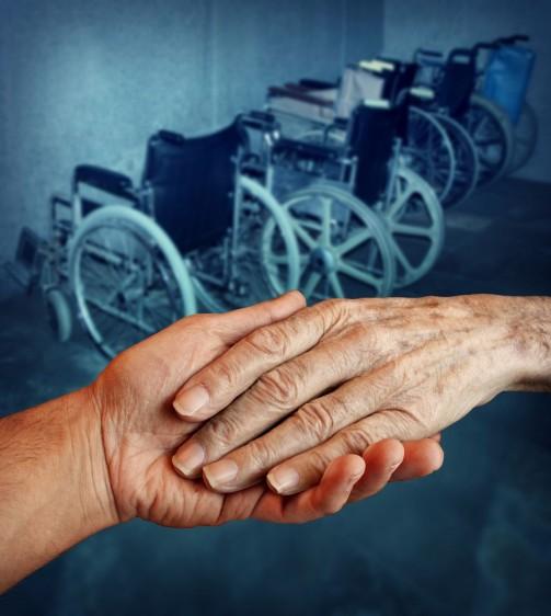 Una mano ayudando a otra al fondo sillas de ruedas