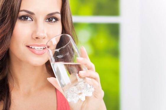 Mujer sosteniendo un vaso con agua en sus manos