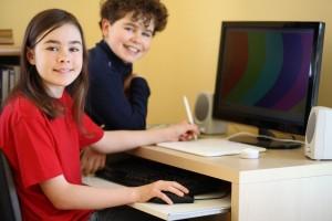 Niña y niño usando una computadora