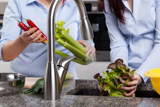 Acercamiento a las manos de un hombre y una mujer lavando verduras