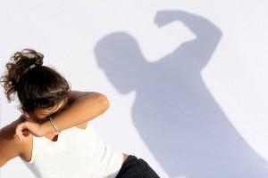Imagen de una mujer cibriendose de una sombra para ilustrar violencia doméstica, abuso conyugal