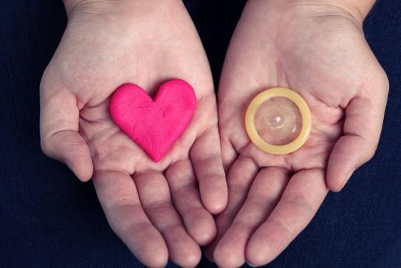 Manos de una mujer mostrando un corazón y en la otra un condón