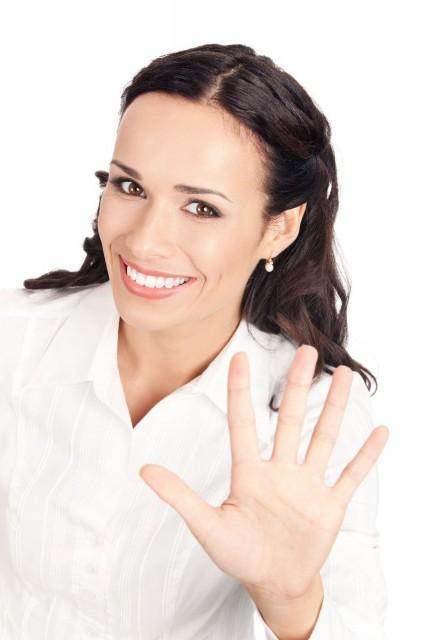 Mujer mostando cinco con sus dedos