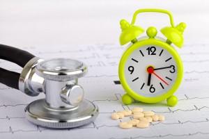 Electrocardiograma con un estetoscopio, un reloj despertador y pastillas