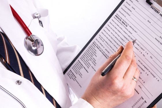 Médico escribiendo datos