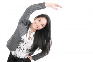 Mujer de negocios haciendo un ejercicio de estiamiento en un fondo blanco