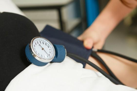 Persona recostada se le mide la presión arterial
