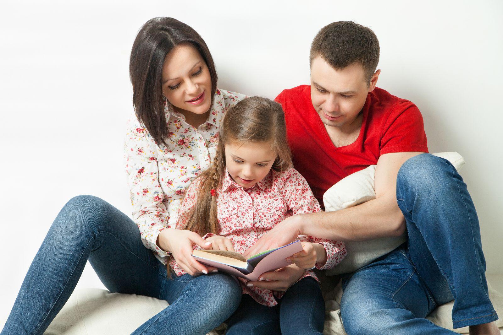 Padre y madre leyendo con una niña