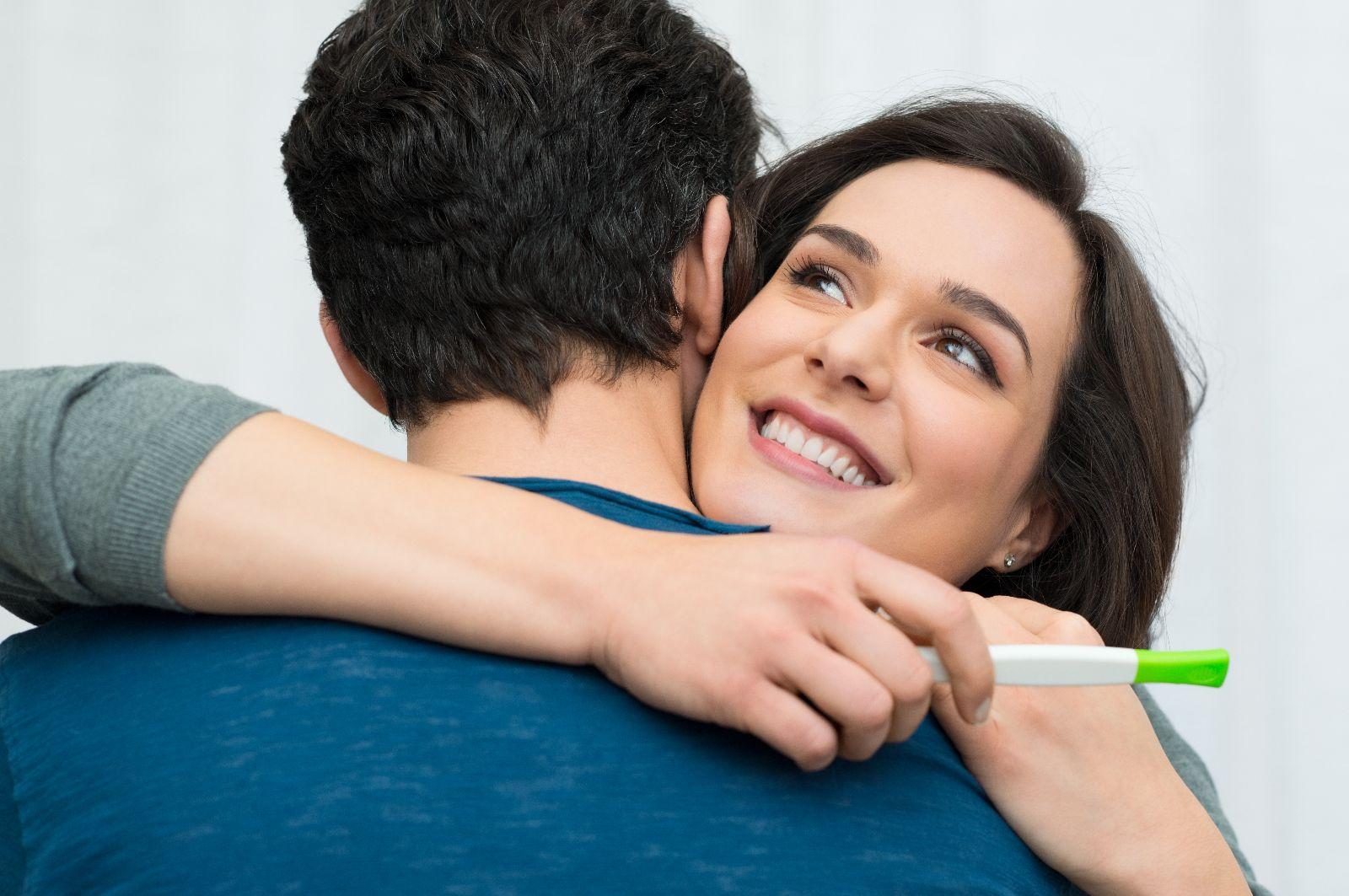 Pareja abrazandose feliz ella sostiene prueba de embarazo en su mano