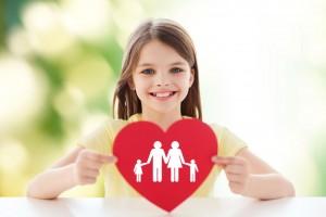 Niña mostrando un corazón rojo que contiene ilustración de familia