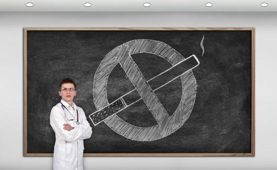 Mpedico al lado de un pizarroncon una ilustración de no fumar