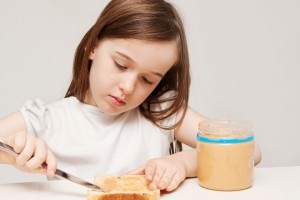 A young girl spreads peanut butter onto a piece of wholemeal bread.