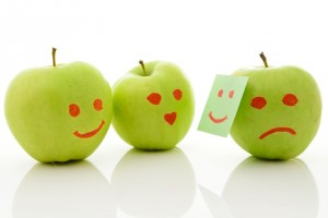 Tres manzanas con rostro una escondiendo tristeza