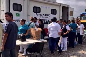 Personas engfrente de una camioneta de servicios del Sector Salud