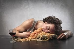 Hombre somnoliento comiendo una cantidad excesiva de espaguetti