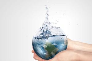 Persona sostiene envas con forma del planeta tierra llenándose de agua