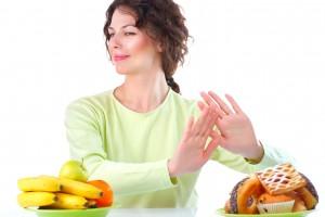 Mujer rechazando productos con alimentos con muchas calorías