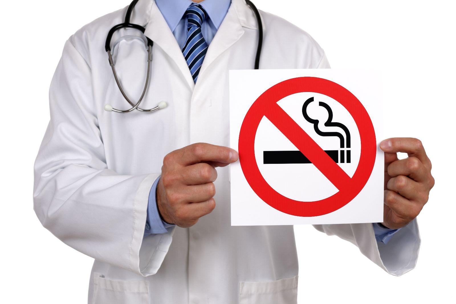 Doctor sosteniendo letrero de no fumar