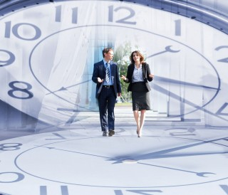 Imagen de un reloj en el centro una imagen de dos ejecutivos caminando