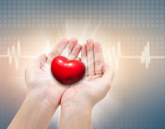 Mujer sostiene figura de corazón con un electrocardiograma al fondo