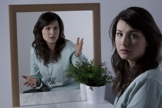 Mujer reflejada en un espejo con actitud diferente