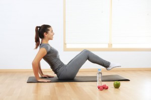 Mujer haciendo ejercicio con agua y frutas al lado