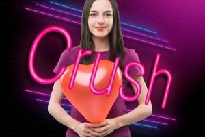 """Mujer con globo en forma de corazón y la palabra """"CRUSH"""" enfrente"""