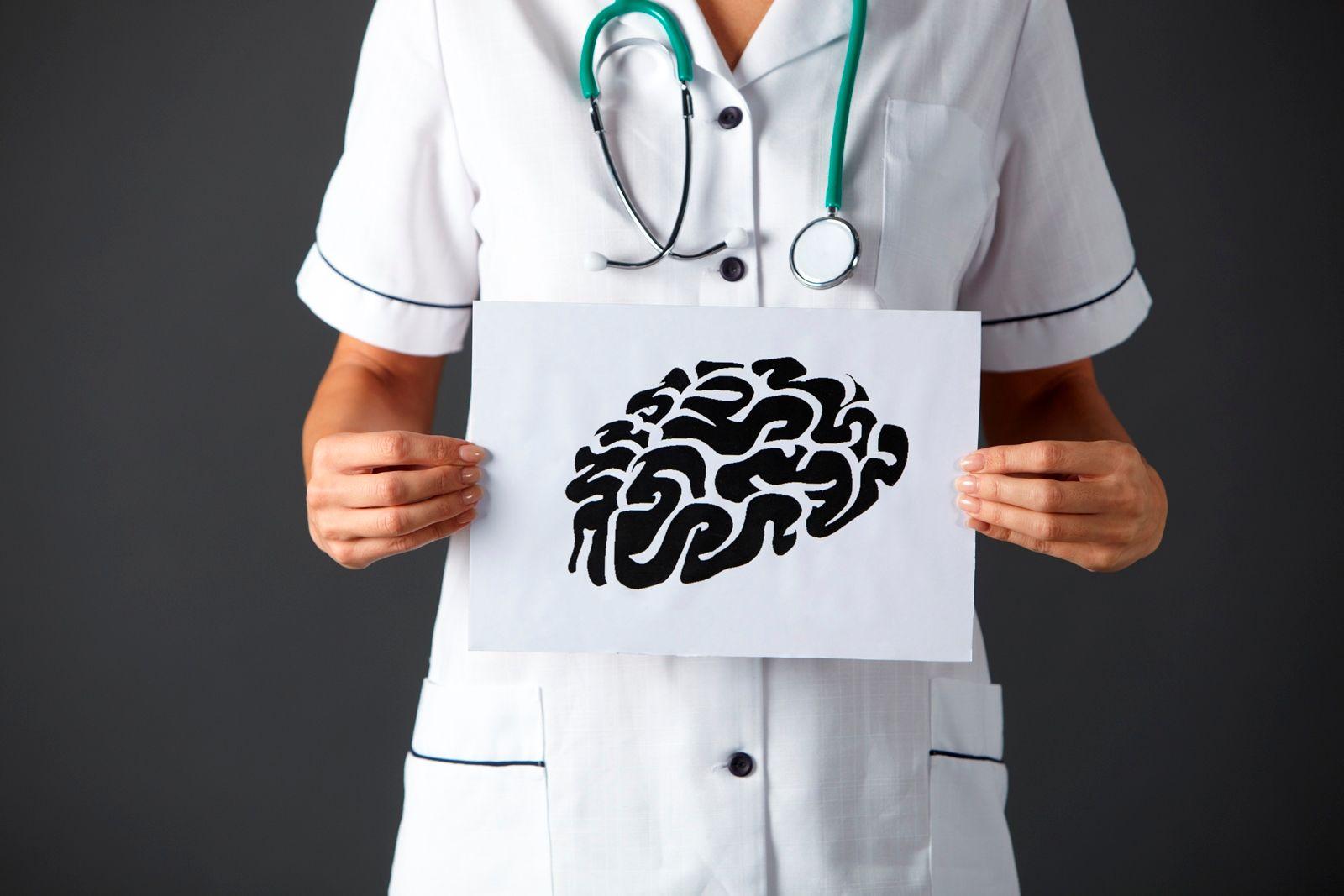 Enfermera sosteniendo letrero con ilustración de un cerebro