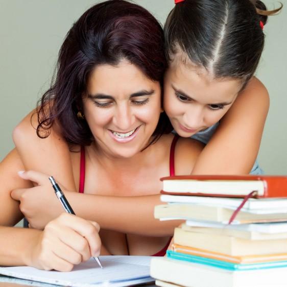 Mujer estudiando en casa mientras su hija la abraza por detrás