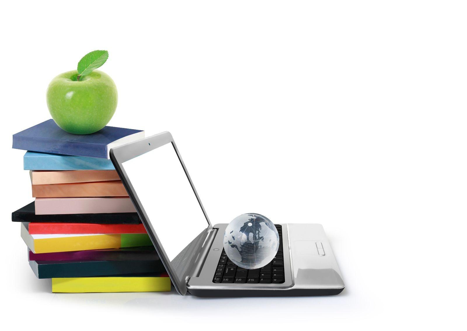 computadora con libros y una manzana
