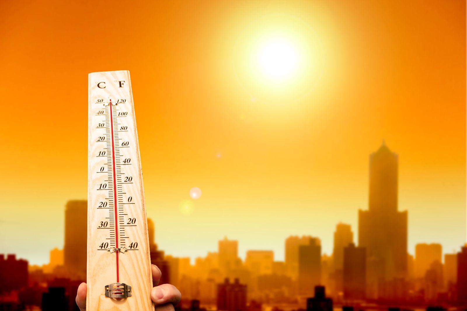 termómetro de mano muestra alta temperatura al fondo una ciudad con un sol