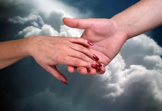 La mano de una mujer alcanzando la mano de un hombre al fondo un cielo nublado
