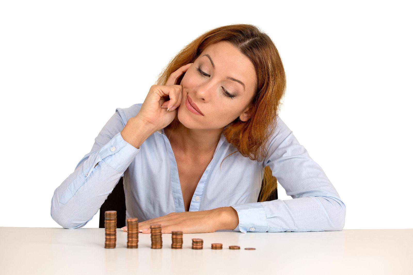 Mujer observa monedas apiladas en forma de grafica de barras