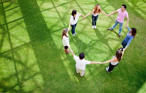Jóvenes agarrados de las manos formando un circulo en un parque