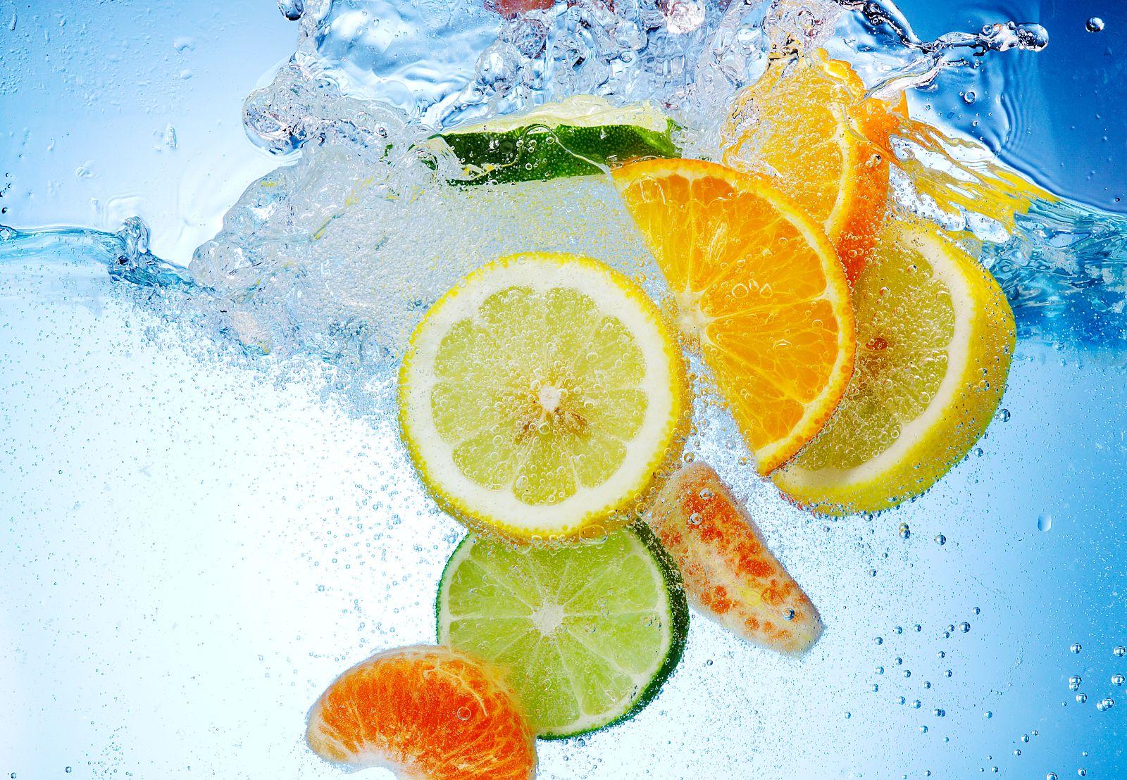 Frutas tropicales cayendo en el agua