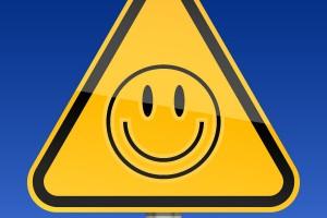 Señal de advertencia amarilla con símbolo de cara sonriente al fondo un cielo azul