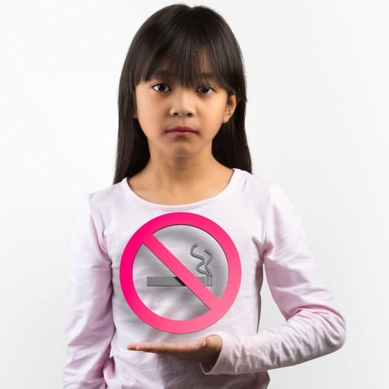 Niña sostienen un letrero de prohibido fumar