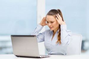 Mujer estresada enfrente de una computadora