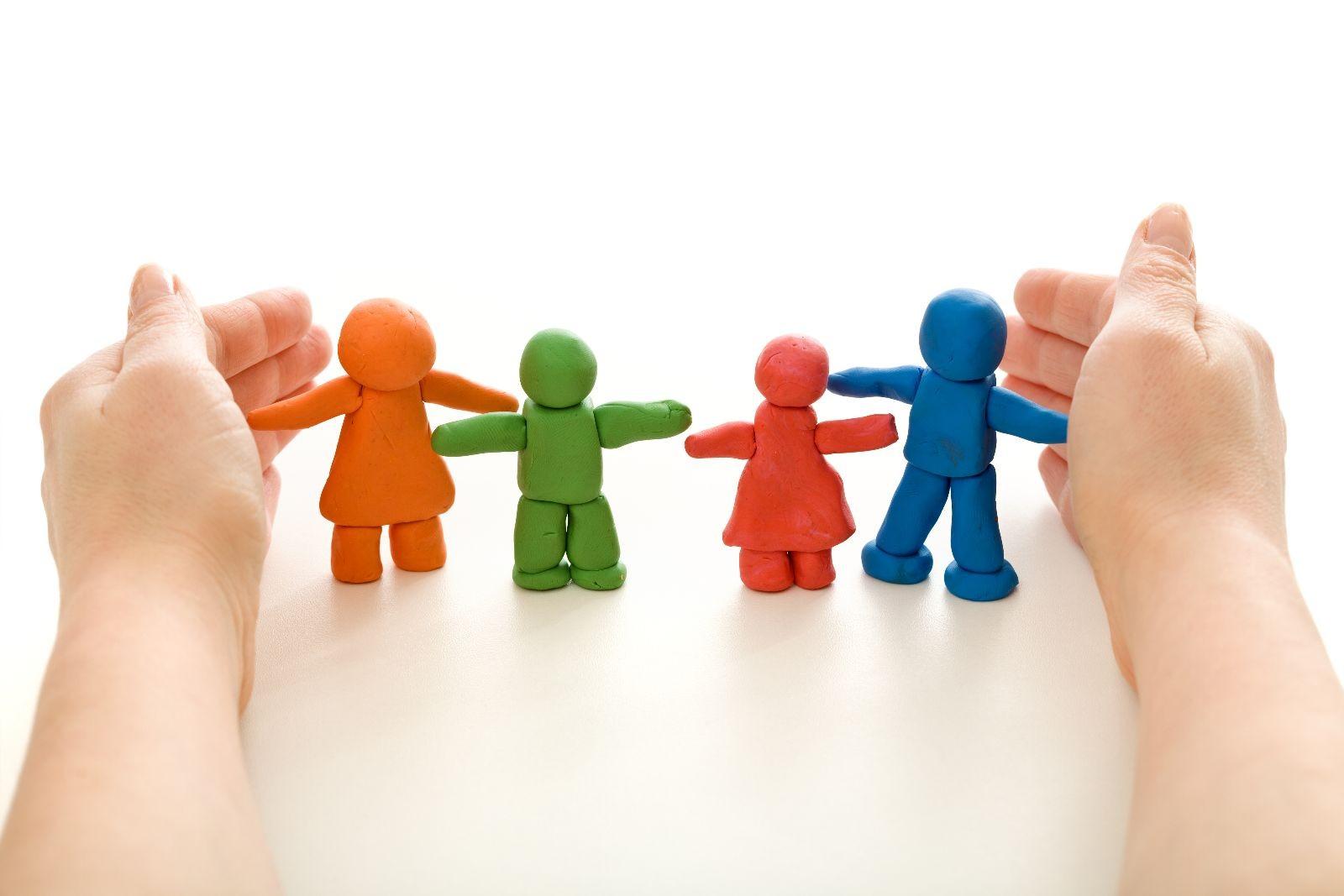 manos cubriendo figuras de personas