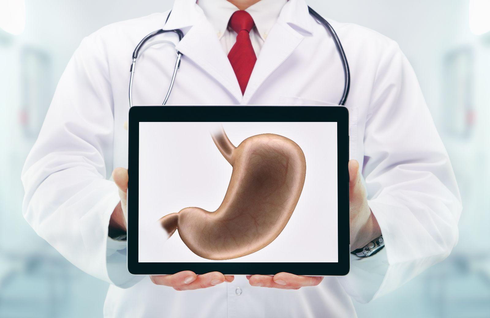 Médico con estetoscopio en un hospital. Con una tablet que muestra una ilustración de un estómago