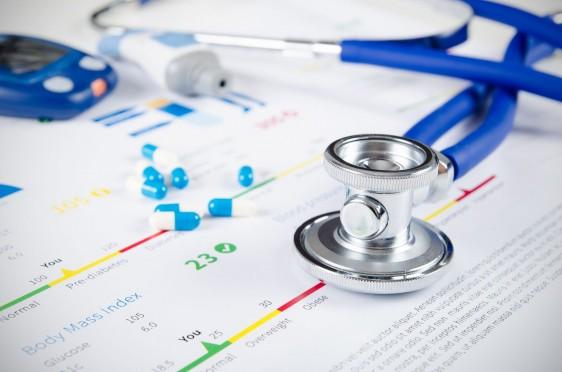 Glucómetro y un estetoscopio sobre documentos médicos