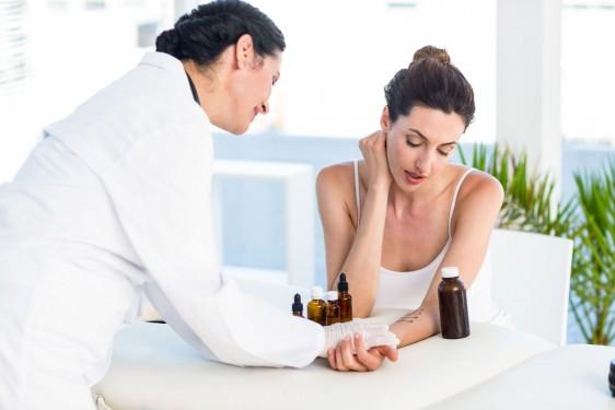 Médico revisando piel de una mujer que extiende el brazo