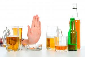 Mano en señal de alto con bebidas con alcohol