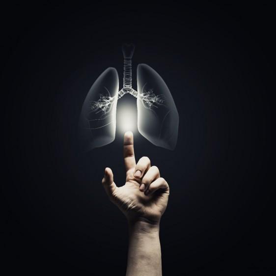 Mano alcanzando un ilustración iluminada de un pulmón en un fondo negro