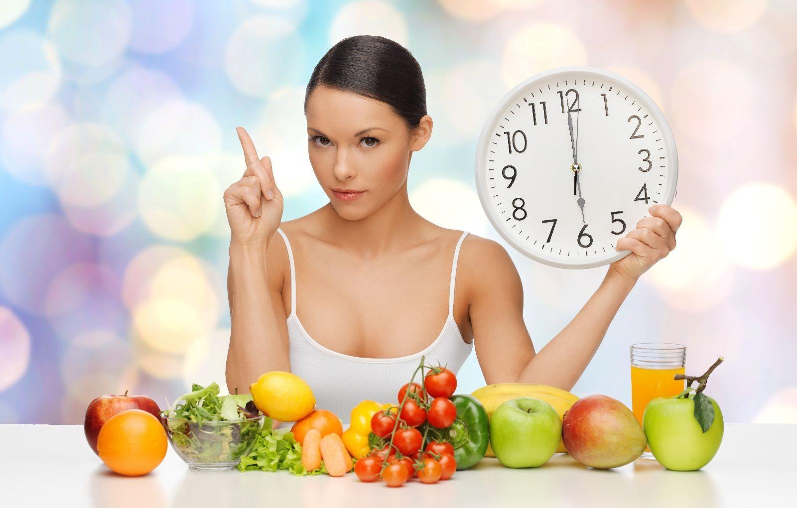 mujer con alimentos saludables y un reloj en su mano