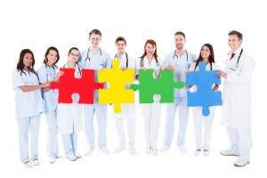 Equipo de médicos sostienen piezas grandes de rompecabezas en sus manos