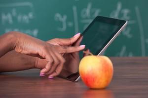 Profesora sostiene tableta digital en el escritorio con una manzana al fondo un pizarrón
