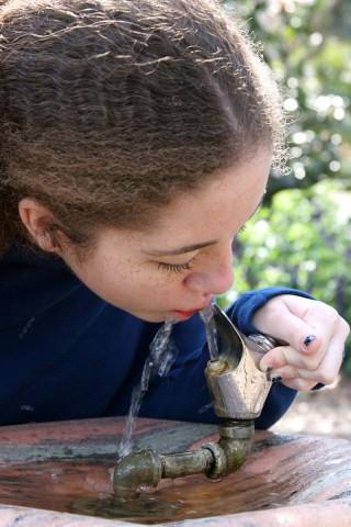 Niña con camisa azul bebiedo agua en un bebedero