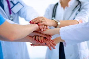 Equipo de médicos apilando las manos