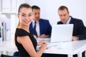 Mujer sonriendo con colegas en el fondo